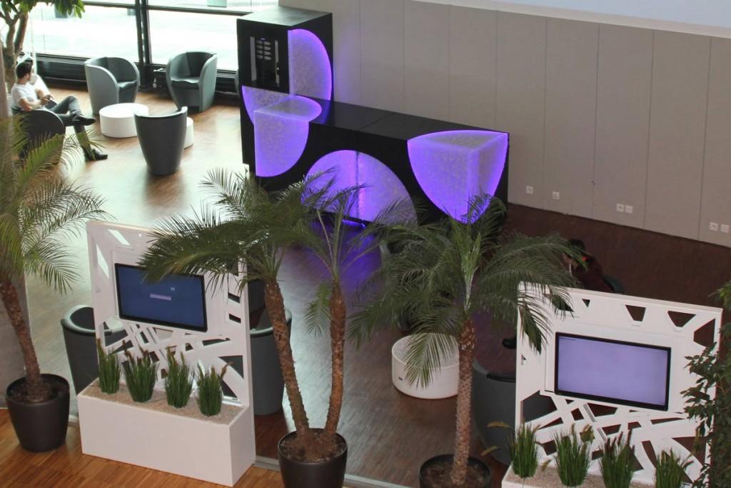 Espace accueil avec tables basses, bureau et machine à café